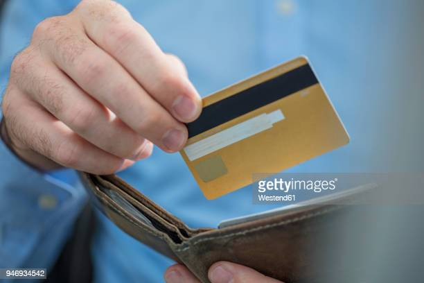 man's hands holding credit card and purse, close-up - gold purse stock pictures, royalty-free photos & images
