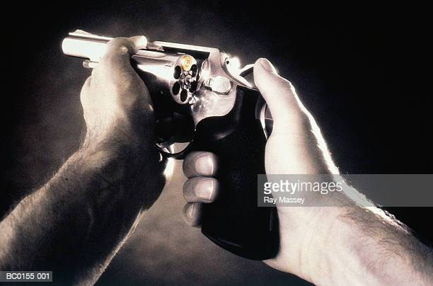 Mans' hands holding handgun loaded with single bullet (tinted B&W)