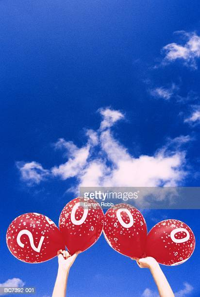 man's hands holding up balloons representing the number 2000 - 2000 stock-fotos und bilder