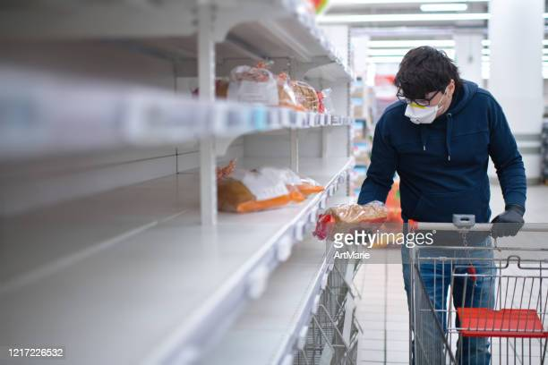 man's hands in protective gloves searching bread on empty shelves in a groceries store - blank stock pictures, royalty-free photos & images