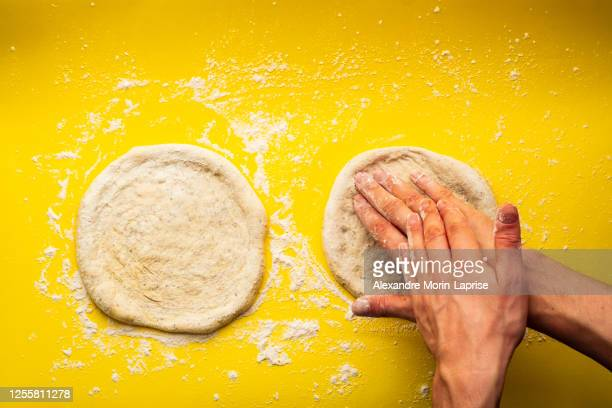man's hands kneading a homemade pizza dough on a yellow background full of flour - dough stock pictures, royalty-free photos & images