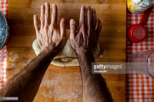 man's hands kneading dough, top view - human arm stock pictures, royalty-free photos & images