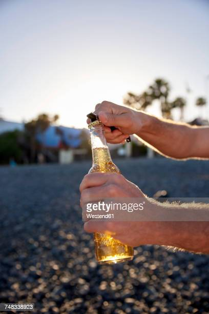 Mans hands opening beer bottle on the beach