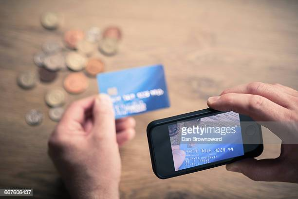mans hands photographing credit card using smartphone - fraud stock pictures, royalty-free photos & images