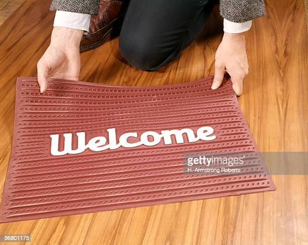 Man's hands placing red rubber welcome mat