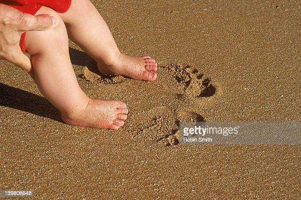 man's hands placing toddlers's feet in larger adult footprints in sand - big foot stock photos and pictures