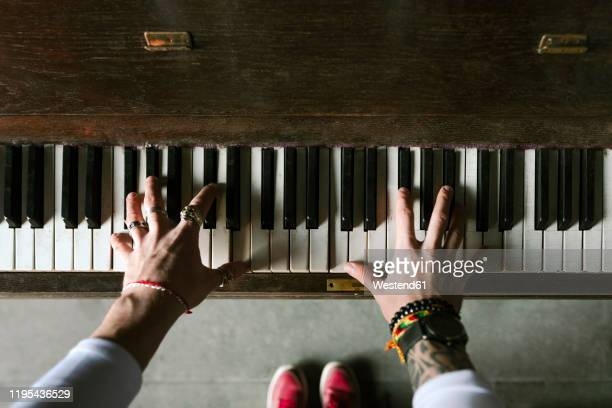 man's hands playing the piano - piano stock pictures, royalty-free photos & images