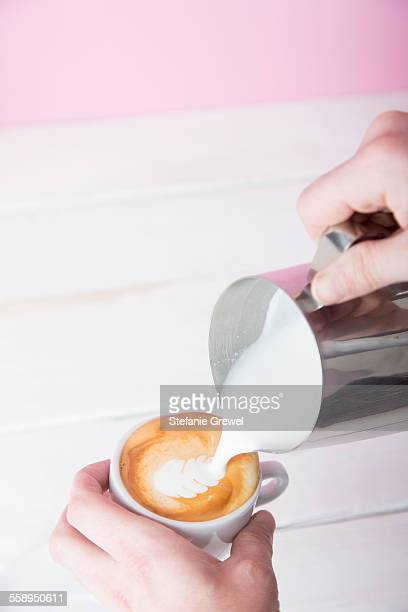 Mans hands pouring frothed milk into coffee cup