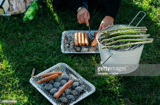 Mans hands preparing barbecue on bucket