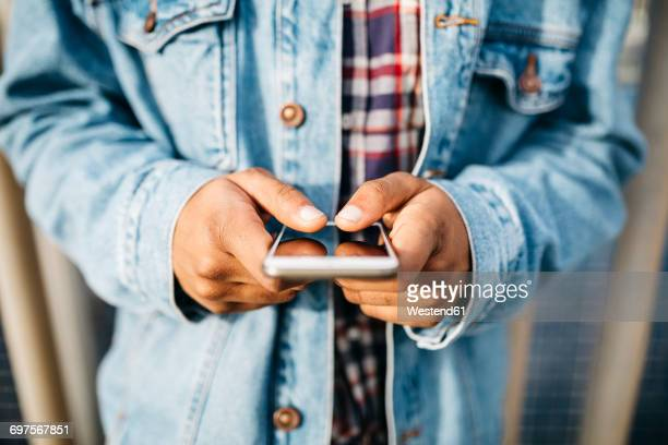 Man's hands text messaging
