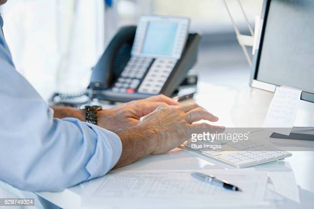 Man's hands typing on computer keyboard