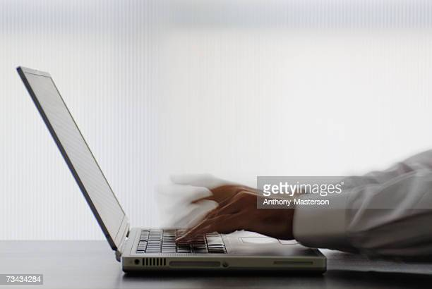 Man's hands typing rapidly on a laptop (blurred motion)