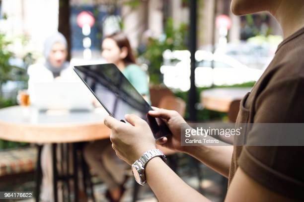 Man's hands using a tablet at an outdoor cafe