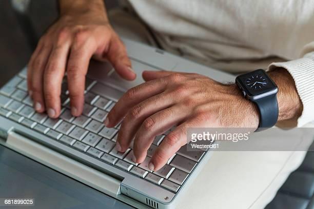 Mans hands using laptop, close-up