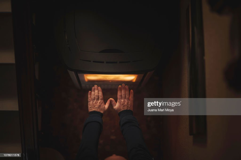 man's hands warming up on an electric stove : Foto de stock