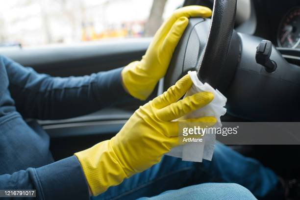 man's hands wearing rubber gloves disinfecting and cleaning car interior - disinfection stock pictures, royalty-free photos & images