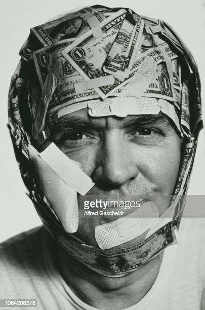 A man's head and face bandaged with plasters of various sizes and American onedollar notes US 1993