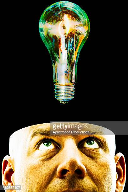 man's head juxtaposed with lightbulb. - blacksburg stock pictures, royalty-free photos & images