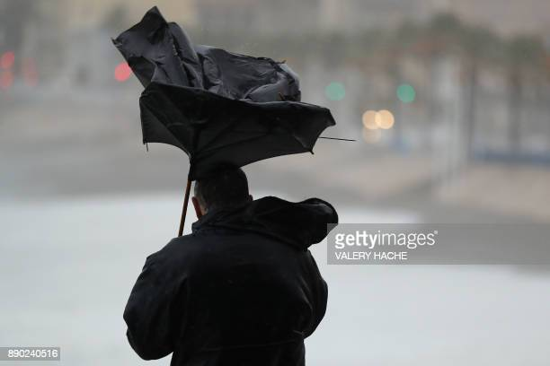 A mans holds a broke umbrella in Nice southeastern France on December 11 as storm Ana smashes into France / AFP PHOTO / Valery HACHE
