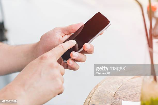Mans index finger typing on display of his smartphone