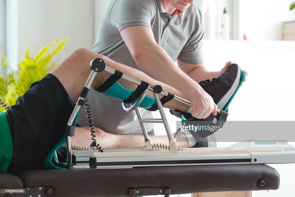 Man's knee rehabilitation in medical center : Stock Photo