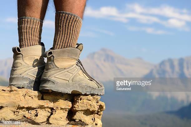 Man's Legs and Hiking Boots On Rocky Peak
