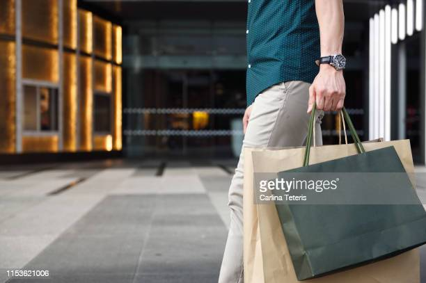 man's legs and shopping bags outside a luxury mall - 買い物袋 ストックフォトと画像