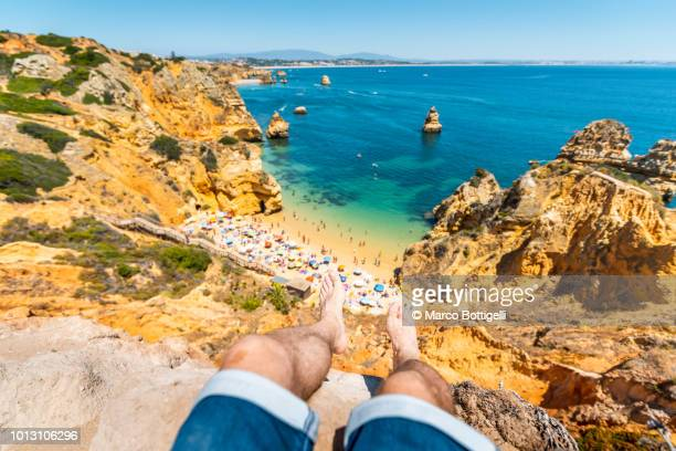 Man's legs barefoot hanging over beach in Algarve, Portugal