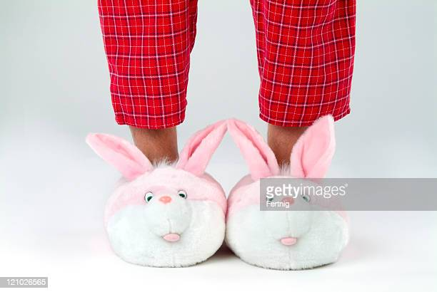 Man's legs in bunny slippers