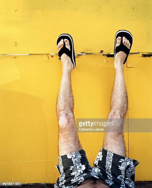 man's legs propped up against yellow wall - hairy man stock pictures, royalty-free photos & images