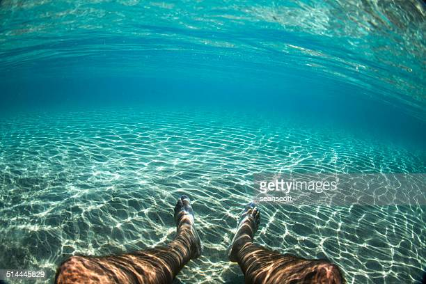 Man's legs underwater in the ocean