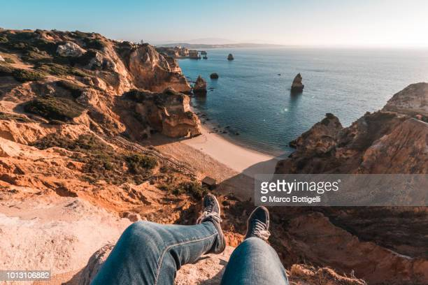 Man's legs wearing shoes hanging over beach in Algarve, Portugal
