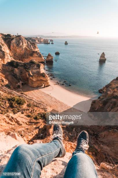 man's legs wearing shoes hanging over beach in algarve, portugal - algarve stock pictures, royalty-free photos & images