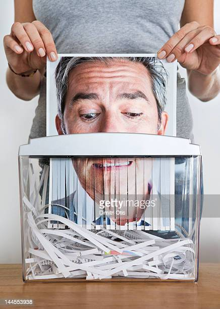 Man's picture being passed through paper shredder