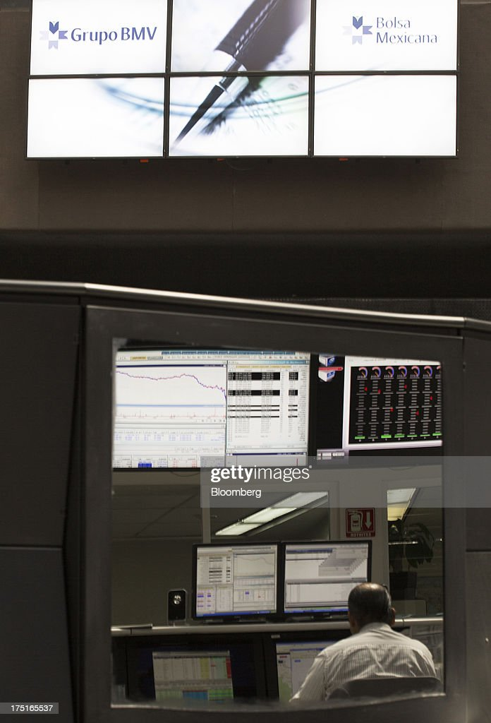 A man's reflection is displayed on a computer screen in the trading gallery of Bolsa Mexicana de Valores (BMV), Mexico's stock exchange, in Mexico City, Mexico, on Wednesday, July 31, 2013. Mexico's economy is forecast to grow 2.8 percent this year based on analyst estimates compiled by Bloomberg. Photographer: Susana Gonzalez/Bloomberg via Getty Images