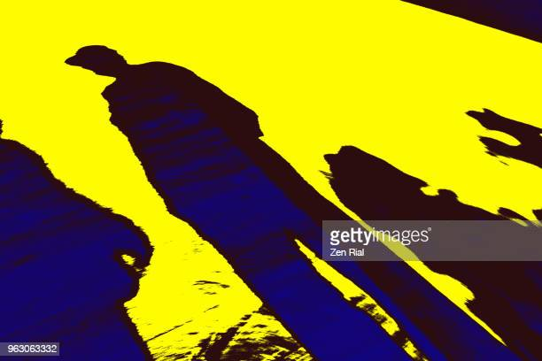man's shadow in black color and blue against bright yellow background - zen rial stock photos and pictures