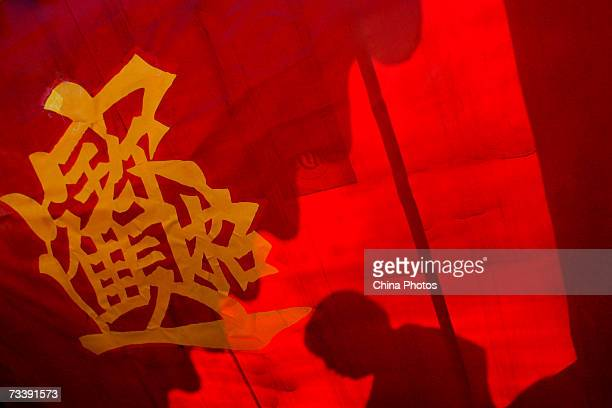 A man's shadow is cast on a red cloth with Chinese