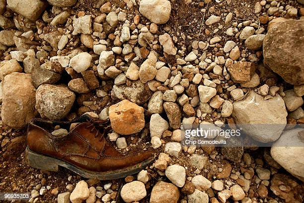 A man's shoe is halfburied at the mass grave site where thousands of earthquake victims are buried February 21 2010 in Titanyen Haiti Bodies have...