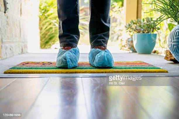 man's shoes covered in shoe protector standing at doorway of home - shoe covers stock pictures, royalty-free photos & images