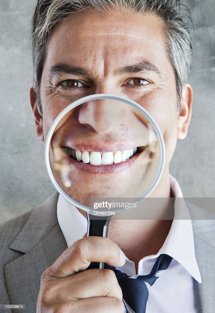 Man's smile enlarged in magnifying glass : Stock Photo