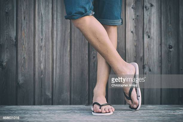 man's summer legs with flip flops - legs crossed at ankle stock pictures, royalty-free photos & images