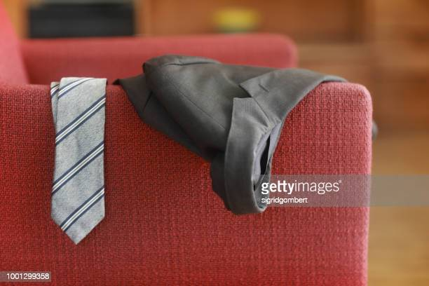 man's tie and jacket hanging on an armchair - coat garment stock pictures, royalty-free photos & images
