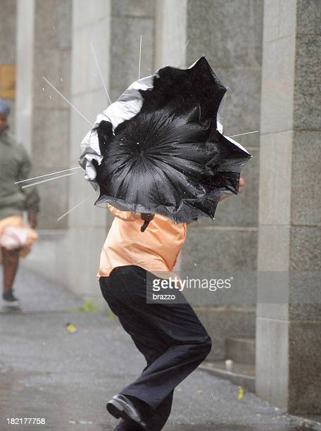 Man's umbrella  is blown inside out in the rain