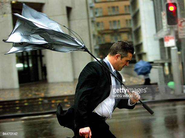 A man's umbrella turns insideout as he battles strong winds and rain in Sydney 30 June 2005 A storm system has dumped more than 100mm of rain in 24...