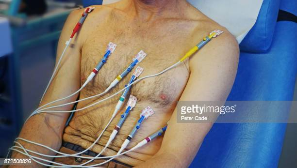 mans upper body undergoing ecg in hospital - cardiac arrhythmia stock pictures, royalty-free photos & images