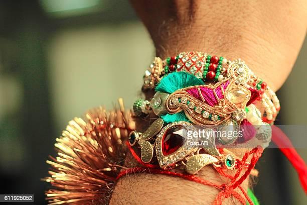 man's wrist with colorful traditional handbands - raksha bandhan stock photos and pictures