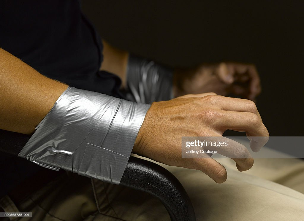 Man's wrists taped to arms of chair, close-up : Stock Photo