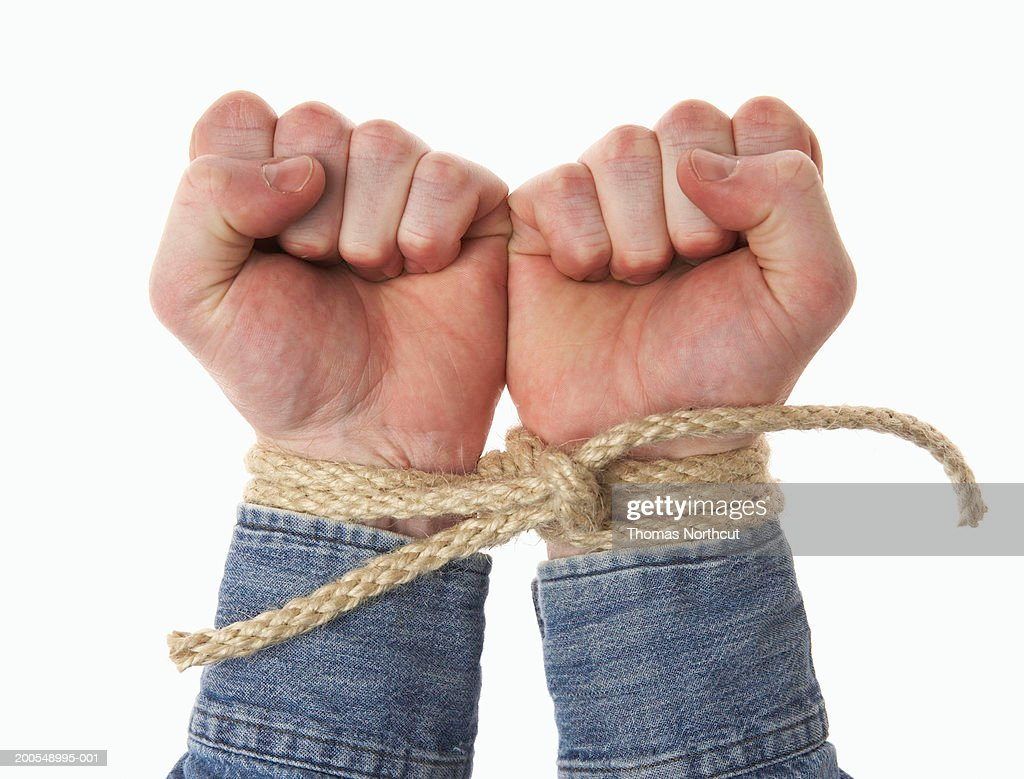 Man's wrists tied together with rope, close-up of hands : Stock Photo