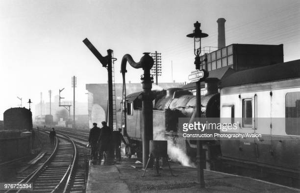 Mansfield Town at Christmastide. In arctic cold the water column is frozen despite the brazier as Stanier 2-6-2T No 40175 stands at the head of a...