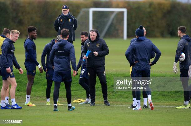 Mansfield Town FC head coach Graham Coughlan speaks with players during their team training session at their training ground in Mansfield, northern...